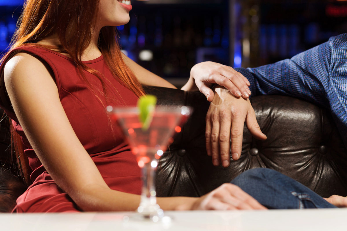 Woman drinking cocktail in gentleman's club